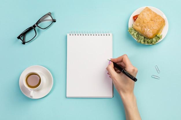 De hand die van een onderneemster op spiraalvormige blocnote met koffiekop en sandwich op het bureau schrijft Gratis Foto