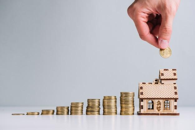 De hand die van een persoon geld in het kopen van huis investeert Gratis Foto
