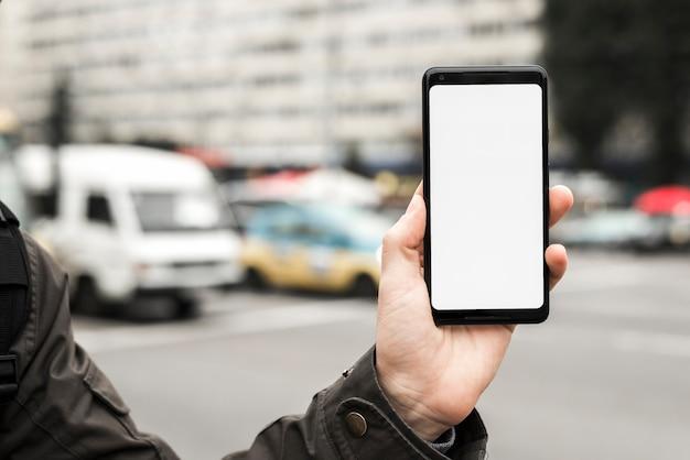 De hand die van een persoon slimme telefoon houden die het witte lege scherm tonen tegen vage weg Gratis Foto