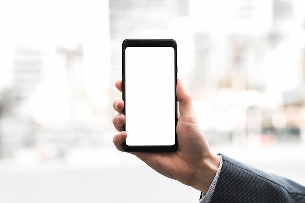 De hand die van een zakenman mobiele telefoon toont tegen vage achtergrond Gratis Foto