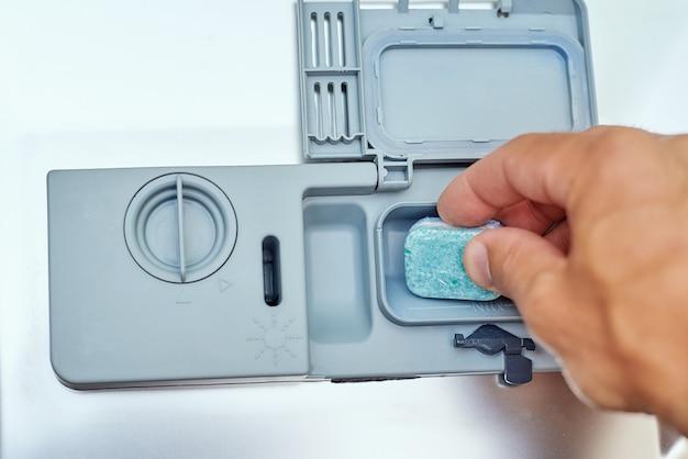 De hand die zeeptablet in de afwasmachinemachine zetten, sluit omhoog. keuken huishoudapparaat concept Premium Foto