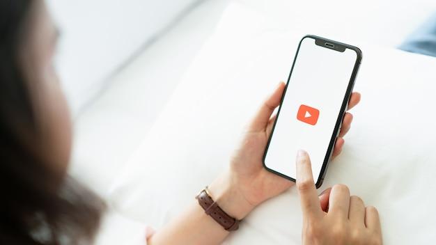De hand drukt op het scherm geeft de pictogrammen van de youtube-app weer Premium Foto