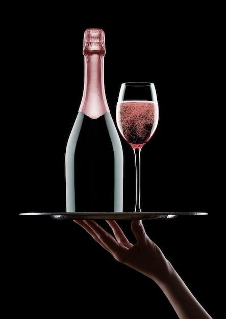De hand houdt dienblad met roze roze champagnefles en glazen met bellen op zwarte achtergrond Premium Foto