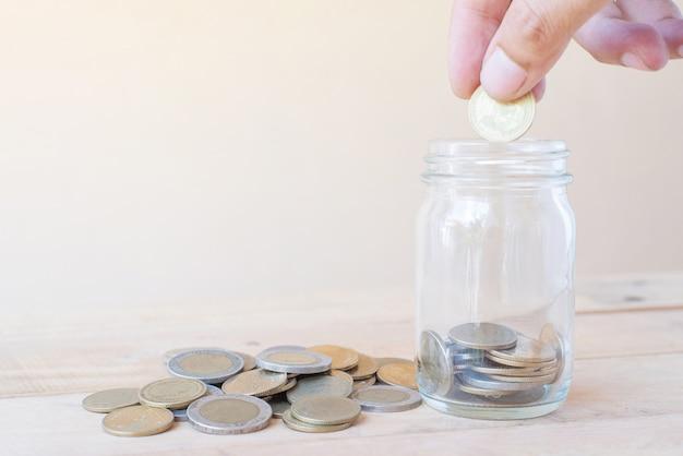 De hand houdt munt en zetten spaarmunten in glas met een stapel van coinson houten tafel - investeringen, business, finance en banking concept Premium Foto