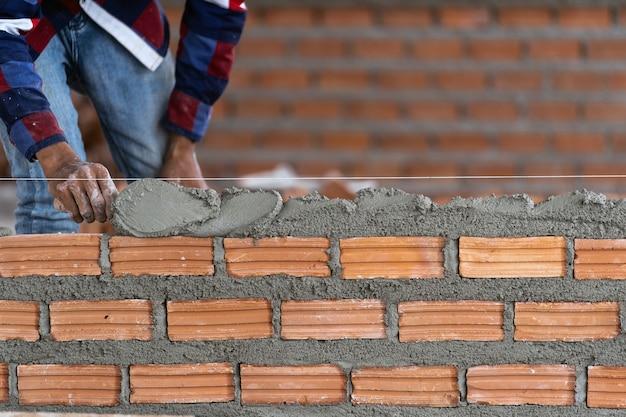 De hand professionele bouwvakker die van de close-up bakstenen in nieuwe industriële plaats legt Premium Foto