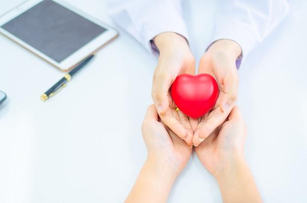 De hand van arts geeft hart aan mensenhand Premium Foto
