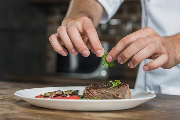 De hand van de chef-kokman die de koriander op voorbereid geroosterd rundvlees versieren Gratis Foto