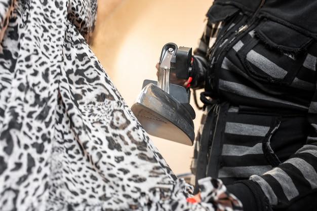 De hand van de close-upvrouw maakt de kleding met een stoomstrijkijzer op een ledenpop glad Premium Foto