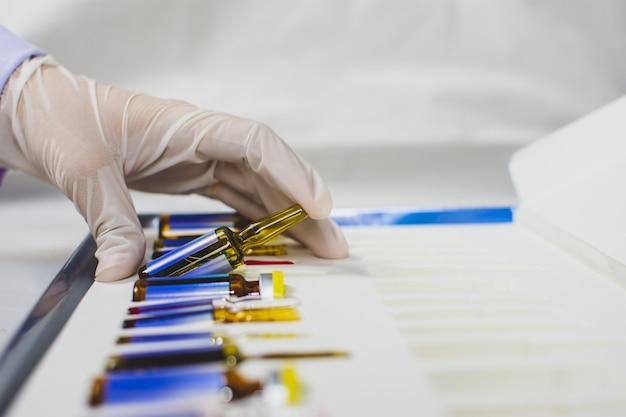 De hand van de dokter pakt de medicijnampulfles uit de doos, het coronavirus-behandelingsconcept, covid-19. Premium Foto