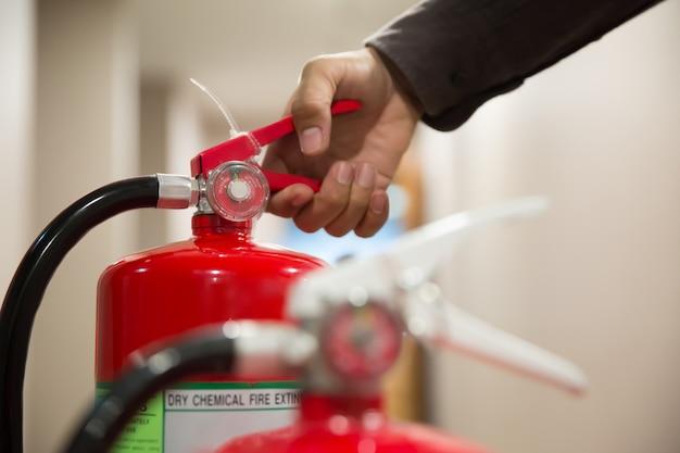 De hand van de ingenieur knijpt in de hendel van de brandblusser. Premium Foto
