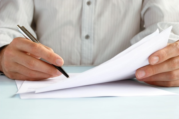 De hand van de man doet aantekeningen in officiële papieren Premium Foto