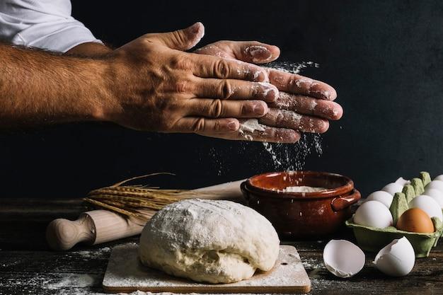 De hand van de mannelijke bakker bestrooit bloem op kneeddeeg Gratis Foto