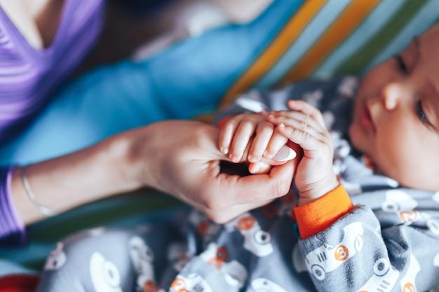 De hand van de pasgeboren baby van de kleine pasgeboren ouder Premium Foto