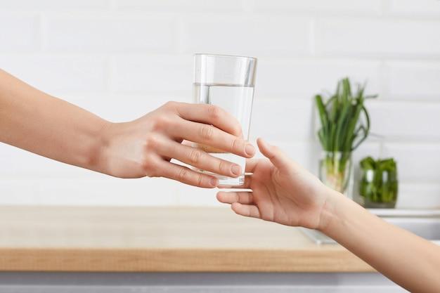 De hand van de vrouw geeft een glas gezuiverd water aan haar kind. conceptzuivering van water Premium Foto