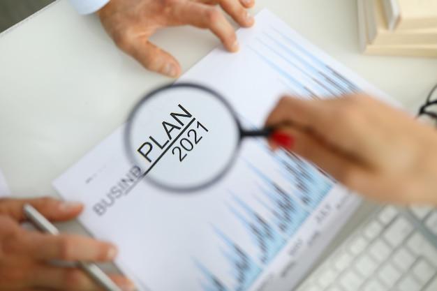 De hand van de vrouw houdt vergrootglas over het businessplan voor 2021 Premium Foto