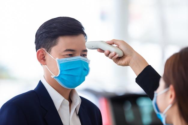 De hand van de vrouw maakt gebruik van een medische digitale infraroodthermometer, gebruikt een lichaamstemperatuurmonitor van een jonge man, het concept van een coronavirus [covid-19] screening. Premium Foto