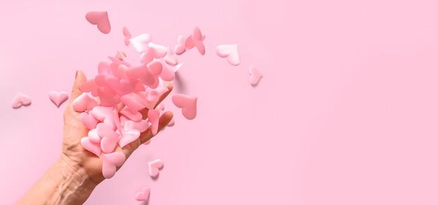 De hand van de vrouw werpt roze satijnen harten op roze. concept liefde. vrouw geeft haar liefde aan de hele wereld. Premium Foto
