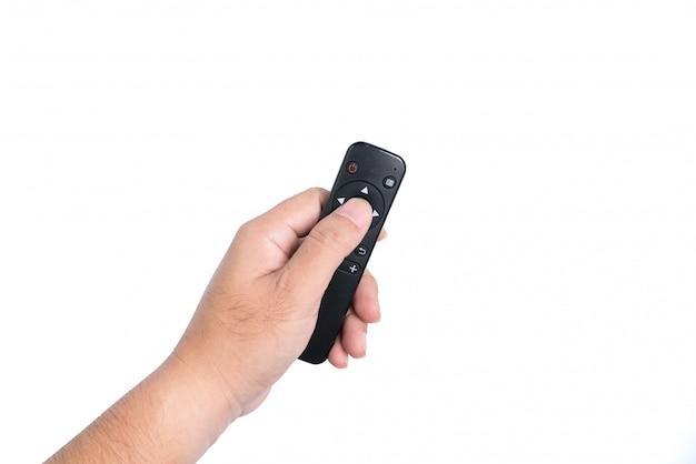De hand van een man houdt een afstandsbediening van een tv vast. Premium Foto