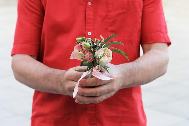 De hand van een man in een rood shirt houdt een klein mooi boeket vast Premium Foto