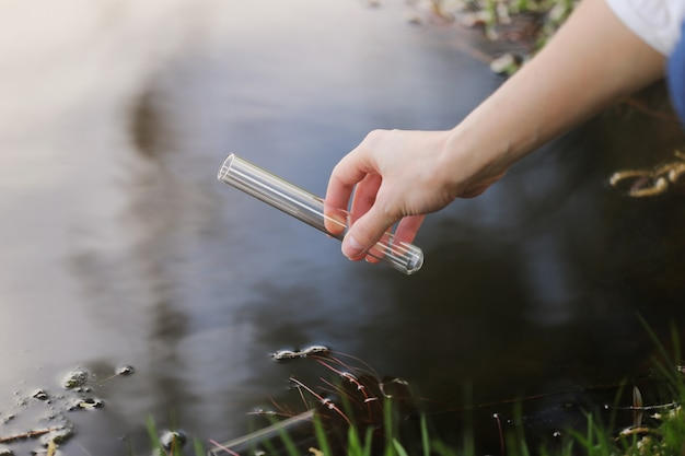 De hand van een specialist zuigt water uit een rivier in een kolf voor verder onderzoek in het laboratorium. controleert het niveau van waterverontreiniging. selectieve aandacht Premium Foto