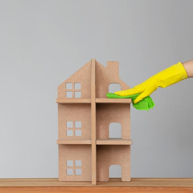 De hand van een vrouw in een rubberen handschoen wast het symbolische huis met een groene doek. het concept van voorjaarsschoonmaak en netheid. Premium Foto