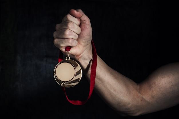 De hand van een vuile man houdt een gouden medaille op een donkere achtergrond. het concept van succes Premium Foto
