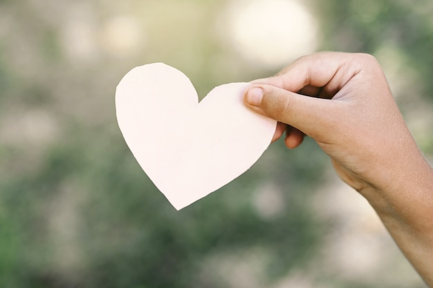 De hand van het kind houdt een hart vast. Premium Foto