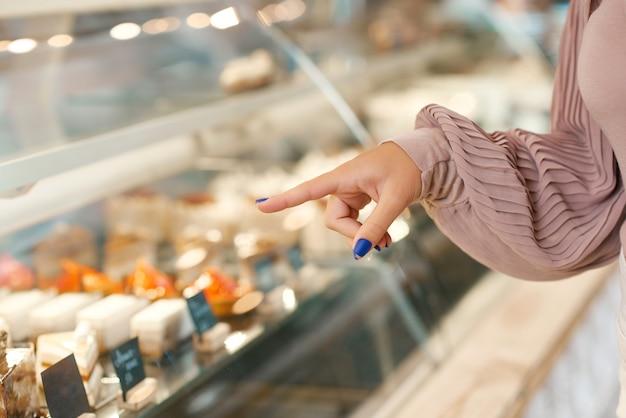 De hand van het meisje met het mooie manicure gebaren, die dessert kiezen van showcase. Premium Foto