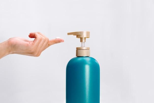 De hand van vrouwen past de veredelingsmiddelfles van het haarshampoo op witte achtergrond toe. Premium Foto