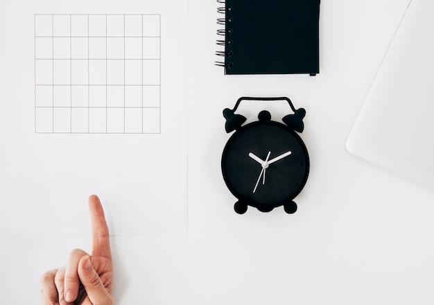 De hand wijzende vinger van een persoon op papier met leeg tijdschema; wekker en dagboek op witte bureau Gratis Foto