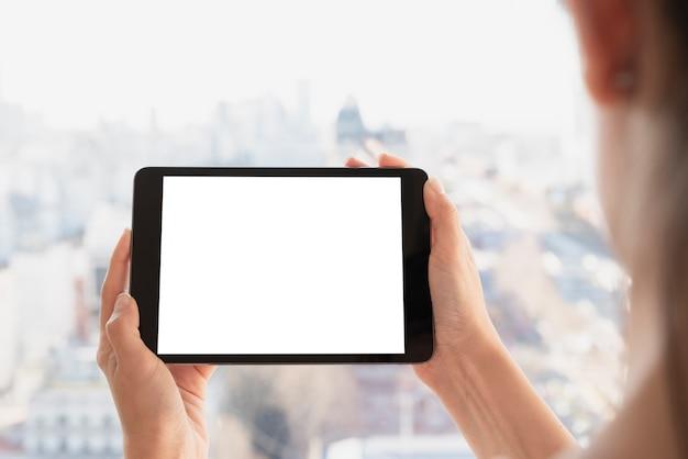 De handen die tablet houden met defocused achtergrond Gratis Foto