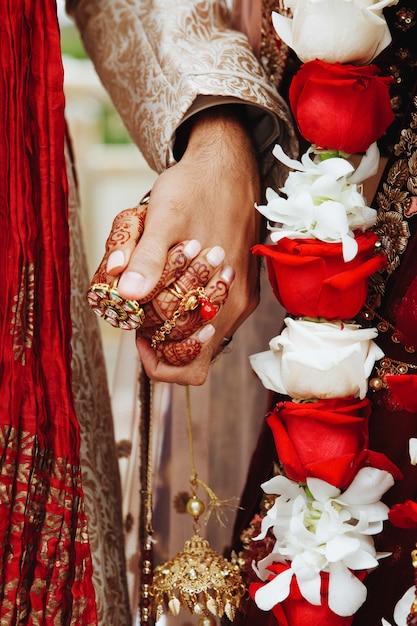 De handen die van de authentieke indische bruid en van de bruidegom in traditionele huwelijkskledij samenhouden Gratis Foto