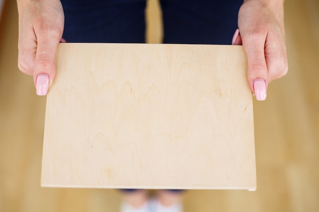 De handen die van de bureauvrouw een boomraad op witte achtergrond houden. copyspace. plaats voor tekst Premium Foto