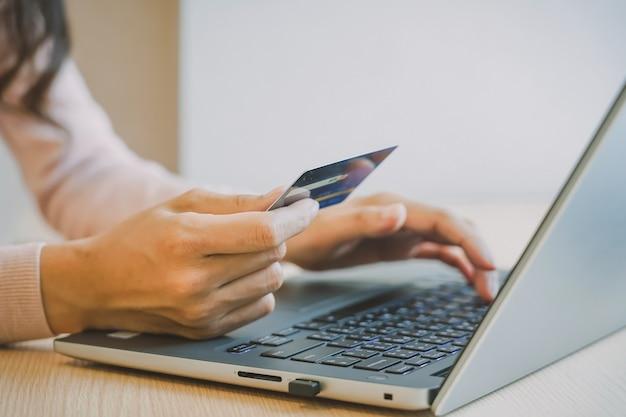 De handen die van de close-upvrouw een creditcard houden en computertoetsenbord gebruiken Premium Foto