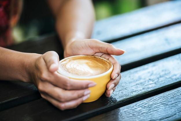 De handen die van de vrouw kop van koffie houden bij koffie Gratis Foto