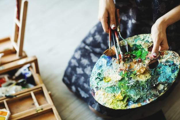De handen die van de vrouw penseel en palet met olieverven houden. detailopname. kunst concept Premium Foto
