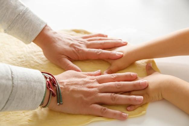 De handen die van een moeder en van een kind samen pizzadeeg uitrekken Premium Foto