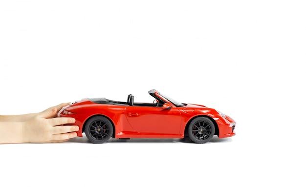 De handen die van kinderen een rode porsche carrera s 911 modelstuk speelgoedauto houden die op witte achtergrond wordt geïsoleerd. Premium Foto