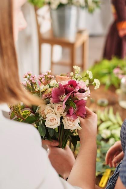 De handen van bloemist verzamelen huwelijksboeket. bloemist op het werk Premium Foto