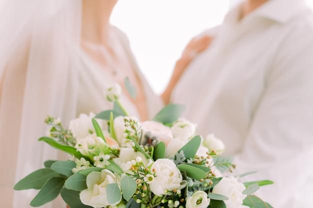 De handen van de bruid houden mooi bruids boeket Premium Foto