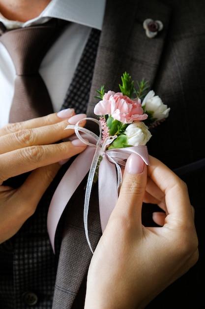 De handen van de bruid passen de boutonniere op het trouwjasje van de bruidegom aan Premium Foto