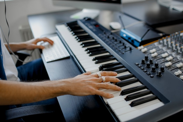 De handen van de componist op pianosleutels in opnamestudio Premium Foto