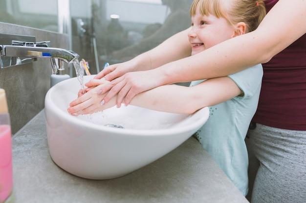 De handen van de moeder van het gewas wassen van vrolijke dochter Gratis Foto