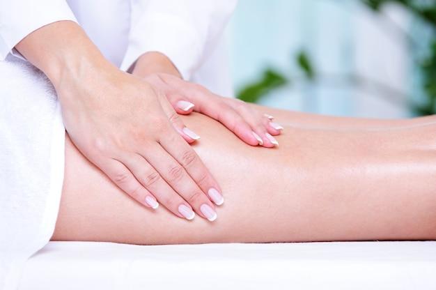 De handen van de schoonheidsspecialiste die massage voor het vrouwelijke been doen Gratis Foto