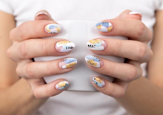 De handen van de vrouw met trendy pastelkleurnagels die kop houden Premium Foto