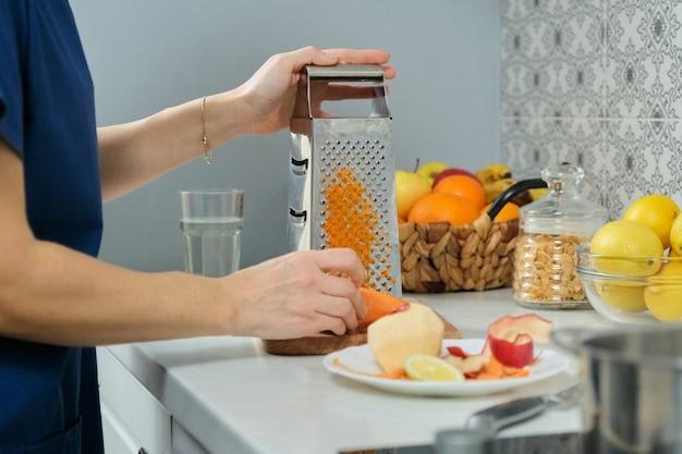 De handen van de vrouw wrijven wortel en appel op metaalrasp in keuken Premium Foto