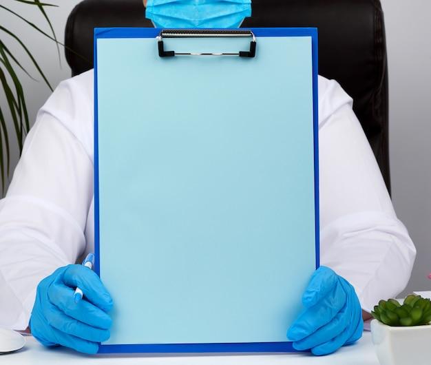 De handen van de vrouwelijke arts in blauwe medische latex handschoenen heeft een map met een paperclip Premium Foto