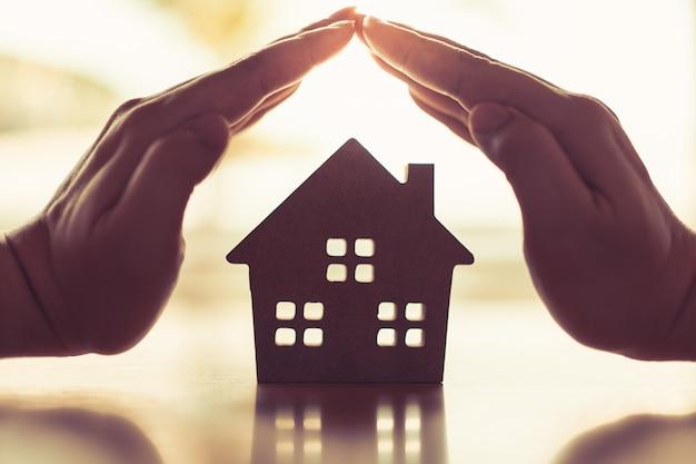 De handen van een jonge vrouw omringen een houten huismodel. Premium Foto