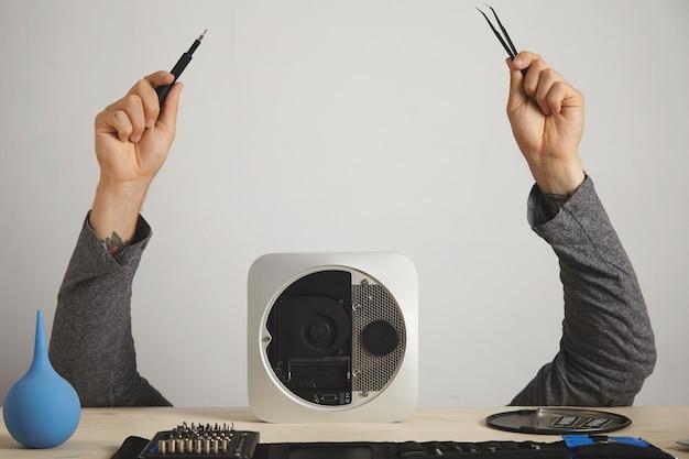De handen van een man met een tang en een schroevendraaier, het hoofd van de man is verborgen achter een computer, op een witte muur Gratis Foto