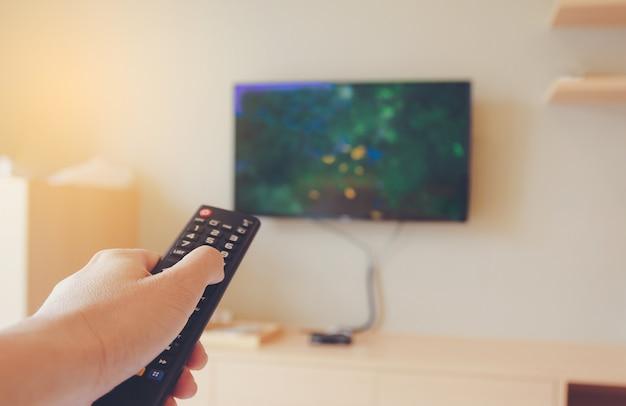 De handen van een man moesten de afstandsbediening in zijn hand kiezen om tv te kijken en te ontspannen. Premium Foto